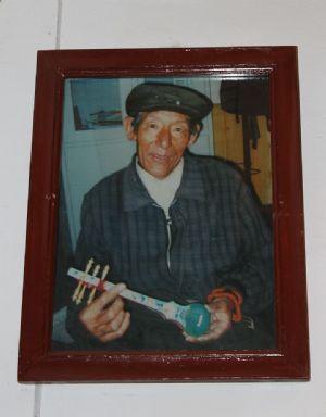 Tibetan artisan holding a model danyen